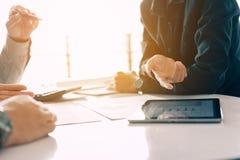 Análise com o PC da tabuleta na reunião de negócios com wor da discussão Foto de Stock