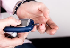 Análise de sangue nivelada de medição da glicose usando o glucometer ultra mini e a gota de sangue pequena das tiras do dedo e de Fotos de Stock
