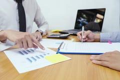 Análise do homem de negócio no papel dos dados com a mulher de negócio na madeira imagens de stock
