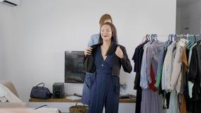 Análise do vestuário As mulheres tentam em equipamentos diferentes, e escolhem o que andar Um amigo ajuda a escolher o melhor video estoque