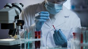 Análisis de sangre del investigador que conduce en el laboratorio médico moderno, atención sanitaria fotografía de archivo