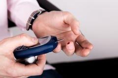 Análisis de sangre llano de medición de la glucosa usando glucometer ultra mini y la pequeña gota de la sangre de tiras del finge Fotos de archivo