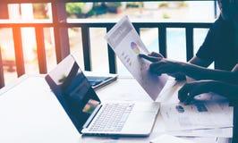 Análisis del equipo del negocio con el gráfico financiero en la oficina, lugar de trabajo imagen de archivo