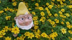 Anão do jardim em uma cama de flor Foto de Stock