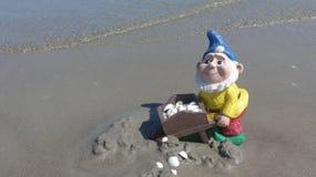 Anão engraçado do jardim com o carrinho de mão na praia imagens de stock