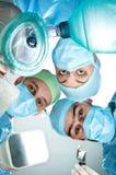 Anästhesiologe drei im Operationsraum mit einer Sauerstoffmaske, einem Defibrillator und einem Blatt für Intubation Stockfotos