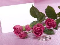 Anéis, cartão e rosas de casamento de prata fotografia de stock