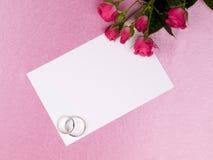 Anéis, cartão e rosas de casamento de prata imagens de stock