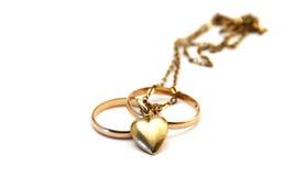 Anéis de casamento e coração dourado Foto de Stock Royalty Free