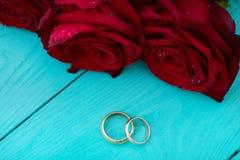 Anéis de casamento e rosas vermelhas Ramalhete do casamento no fundo de madeira azul Foco seletivo Copie o espaço Zombaria acima  imagem de stock royalty free