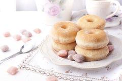 Anéis de espuma com açúcar em uma placa em um fundo claro Os doces da caloria para o café da manhã livram o lugar Vista superior foto de stock