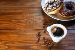 Anéis de espuma vitrificados chocolate com café da caneca imagens de stock
