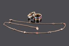 Anéis de ouro com esmalte e a corrente dourada no fundo reflexivo escuro Foto de Stock Royalty Free