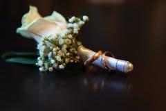 Anéis de ouro do arranjo de flor do casamento imagem de stock