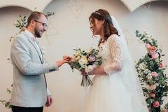 Anéis de ouro do casamento da troca dos noivos fotografia de stock