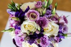 Anéis de ouro do casamento em um ramalhete das flores foto de stock