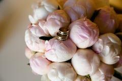 Anéis de ouro do casamento em um ramalhete das flores foto de stock royalty free