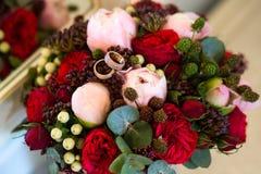 Anéis de ouro do casamento em um ramalhete das flores imagem de stock royalty free
