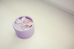 Anéis de ouro do casamento na caixa roxa no fundo branco fotografia de stock royalty free