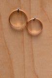 Anéis de ouro na textura de madeira Foto de Stock Royalty Free