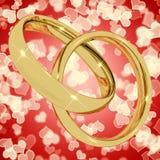 Anéis de ouro no fundo de Bokeh do coração Imagens de Stock Royalty Free