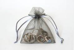 Anéis de prata em um saco da malha Fotos de Stock