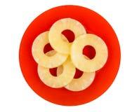 Anéis do abacaxi enlatado na placa vermelha isolada no branco imagem de stock royalty free