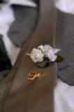 Anéis do boutonniere & de casamento dos noivos imagem de stock