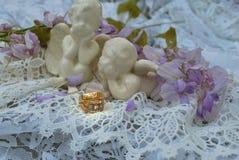 Anéis dourados com 2 anjos e laços Imagem de Stock