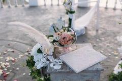 Anéis dourados do casamento decorados com as flores no fundo branco no vidro grande Fotos de Stock