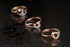 Anéis dourados em um fundo preto Fotografia de Stock Royalty Free
