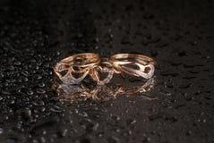 Anéis dourados em um fundo preto Imagens de Stock Royalty Free