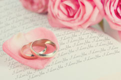 Anéis dourados na pétala cor-de-rosa cor-de-rosa no livro aberto fotografia de stock
