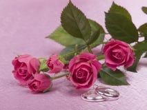 Anéis e rosas de casamento de prata fotografia de stock