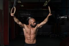 Anéis musculares de Hanging On Gymnastic do atleta fotos de stock royalty free