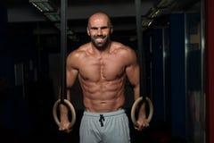 Anéis musculares de Hanging On Gymnastic do atleta imagens de stock royalty free