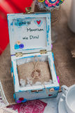 Anéis na caixa de madeira rústica com botões em um pano de saco Ramalhete do casamento de feltro feito a mão na guita de vidro Jo Foto de Stock Royalty Free