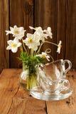 Anémones blanches et deux tasses et soucoupes en verre sur le backgrou en bois Image stock