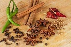 Anís de estrella, chile verde, pimienta, canela y otras especias - fondo de madera Foto de archivo libre de regalías