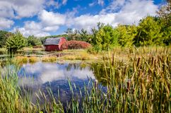 An Abandoned Red Sinking Barn Sinks Into A Lake Near Zimmerman, Minnesota On Sunny Day Stock Photos