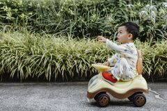 Free An Adorable Toddler Asian Boy 1-year-old Siting And Enjoy To Play Ride-on Toys Outdoor In The Garden With Grass Background Royalty Free Stock Photo - 192060345
