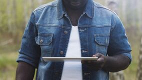 Free An African Man Using The Tablet In The Forest. Wireless Or Future Technology Concept. Stock Photography - 194399562