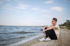 Free An Attractive Fellow In A White T-shirt Sitting On A Riverbank On A Natural Blurred Background. Stock Photo - 99372940