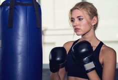 Free An Attractive Woman Guarding And Punching On A Sand Bag At The G Royalty Free Stock Photos - 121044258
