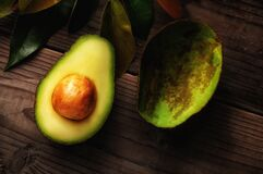 Free An Avocado Cut In Half On A Wood Surface With Leaves. One Half Shows The Seed While The Other Has Been Scooped Out Stock Image - 190873631