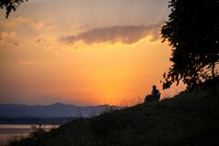 Free An Elderly Couple Sits On Chairs By The Lake And Looks At The Orange Sunset. Stock Photos - 176720533