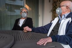 Free An Elderly Couple Wearing A Protective Mask And Holding Hands. They Are Sitting At Terrace Of Their House In Brescia, Lombardy, It Royalty Free Stock Photos - 178561518
