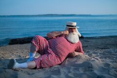 Free An Elderly Man In A Striped Retro Swimsuit Sunbathes On The Beach. An Old Gray-haired Bearded Man In A Hat Lies On The Royalty Free Stock Photo - 190817255