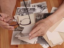 Free An Elderly Woman Looks At Old Photographs, Recalls Her Past Youth. Hands On The Table. Loneliness,, Memories Royalty Free Stock Image - 161345646