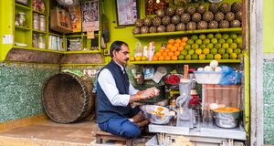Free An Indian Man Peeling Fruits In His Colorful Juice Shop On The Streets Of The City Of Royalty Free Stock Photography - 214751727